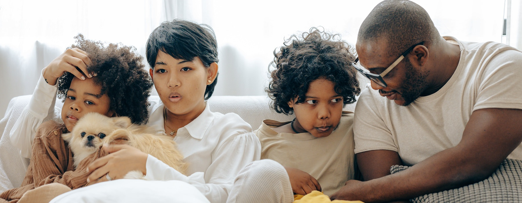 young ethnic family sits on living room couch together